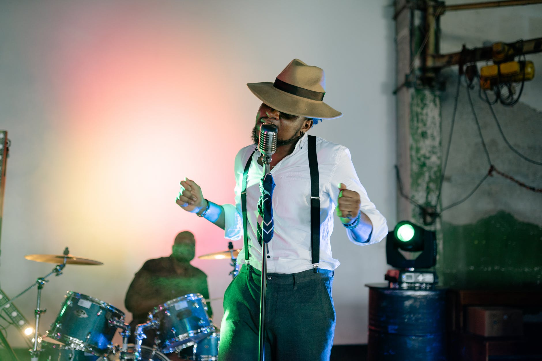 man in white shirt and hat standing and singing